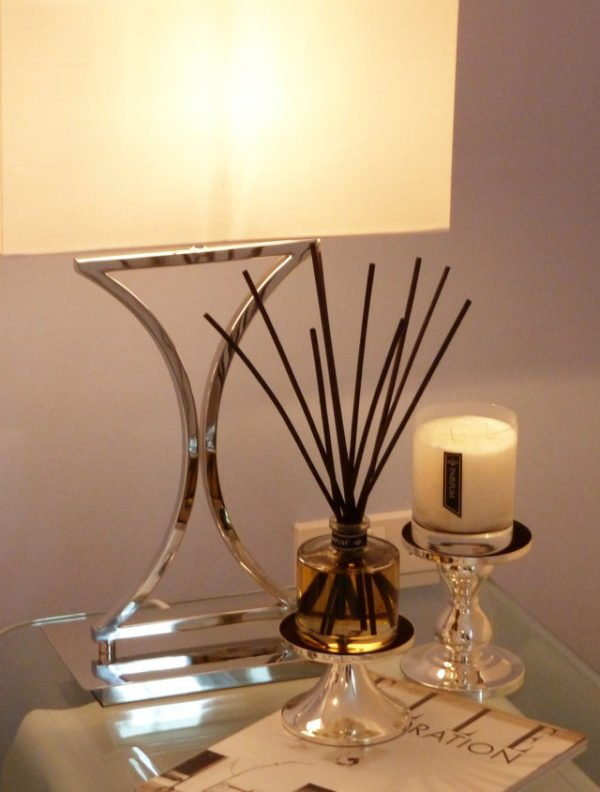 PAIRFUM luxury scented candle and natural reed diffuser on a bedside table in modern house with Elle Decoration