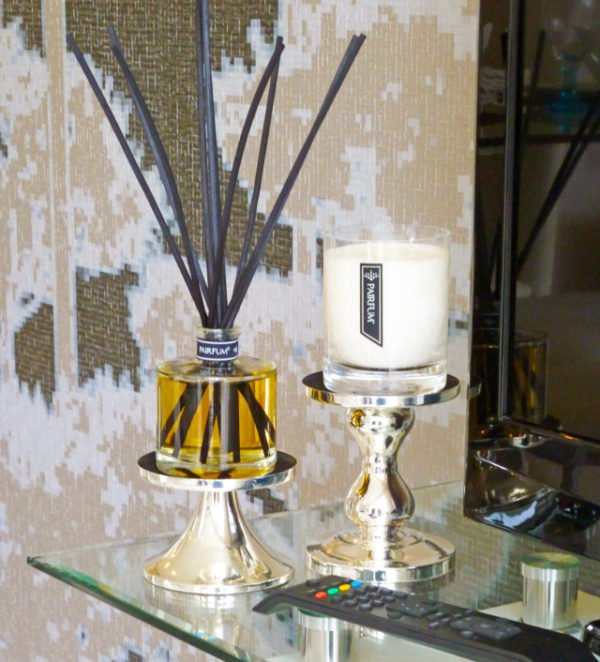 PAIRFUM luxury scented candle and natural reed diffuser on a console table