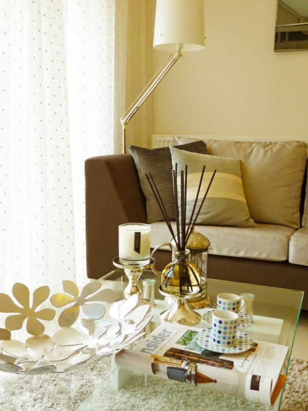 PAIRFUM luxury scented candle and natural reed diffuser on a coffee table in a modern house