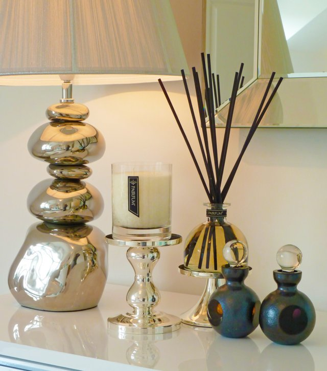 PAIRFUM luxury scented candle and natural reed diffuser on a side table. Fragrance Layering in your home.