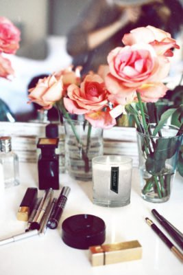 PAIRFUM natural, luxury scented candle on dressing table with perfume and make-up beside roses in a glass