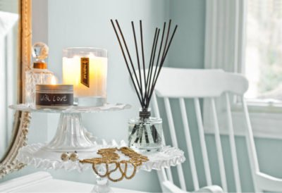 PAIRFUM luxury scented candle and natural reed diffuser on a side table in a Nordic style house